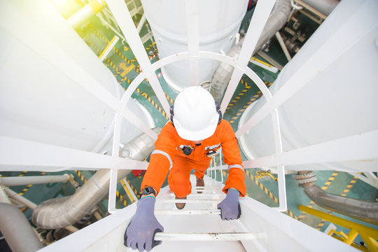 Production operator climb up to oil and gas process plant to observer gas dehydration processing at offshore oil and gas central processing platform.