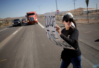 A protestor carrying a sign crosses a road as she marches during a protest against the construction of a shelter for migrant children on the outskirts of El Paso, Texas