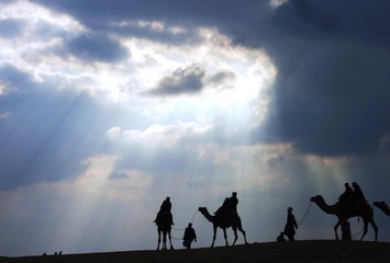 Silhouette People And Camels Against Cloudy Sky