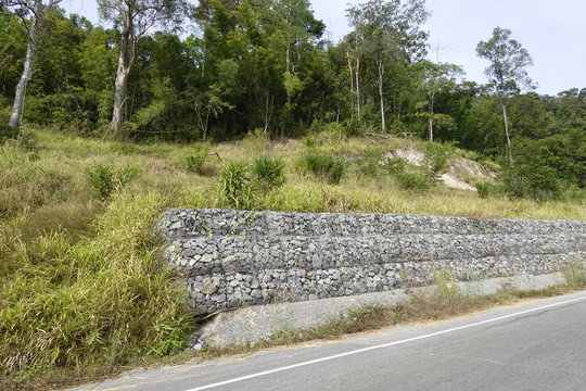 The construction of stone walls, to prevent soil erosion on the mountainside