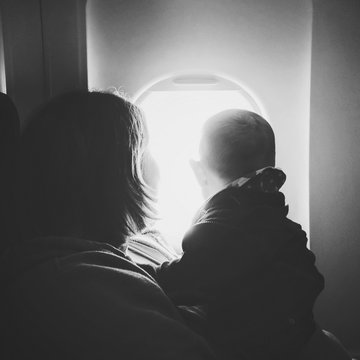 Close-Up Of Mother And Son Looking Through Window While Traveling In Airplane