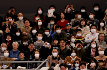 Visitors wearing surgical masks attend the opening ceremony of the Ariake Arena, which will host volleyball and wheelchair basketball competitions in Tokyo 2020 Olympic Games in Tokyo