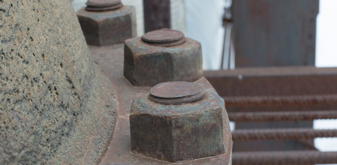 Large rusty nuts on a latch. Stop valves of large sizes.