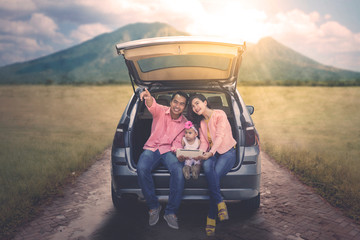 Parents and daughter sitting behind the car