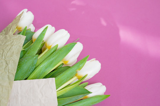 A bouquet of white tulips and a red velvet heart on a pink background-the concept of Valentine's Day.