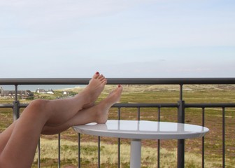 Low Section Of Woman Relaxing On Table By Railing Against Sky Fototapete
