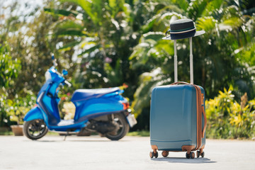 A stylish new SUITCASE with a hat stands in the open air against a background of tropical greenery and a motorbike. Vacation and travel concept.