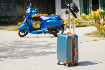 Blue new SUITCASE with a black hat, stands on the street, against a background of tropical Palm trees, a scooter and a hotel complex. The concept of vacation and travel in Thailand.