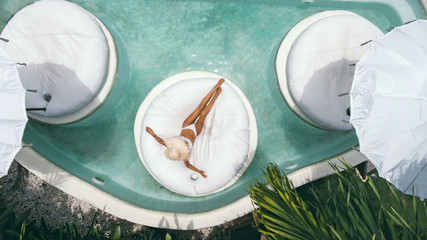 Woman relaxing in clear pool water in hot sunny day on Bali villa