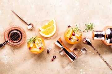 Orange Cranberry Rosemary and Vodka cocktail, copper bar tools, beige background, hard light, top...