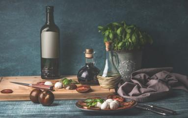 Fototapeta Food still life with oil bottles, mozzarella,  tomatoes and kitchen herbs in pot on kitchen table background obraz
