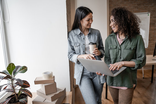 Teamwork in office, women work with laptop. Young small business owners, selling online on a website. Online Sales, E-Commerce, Online Business, with postal parcel, selling online, delivery concept.