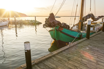 Historic fishing boat anchoring in the harbour during a scenic sunset