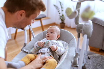 Handsome caring caucasian young father playing with his adorable 6 months old son. Baby lying in baby rocker chair and feeling satisfied.