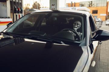 Skeleton in car, fueling on gas station