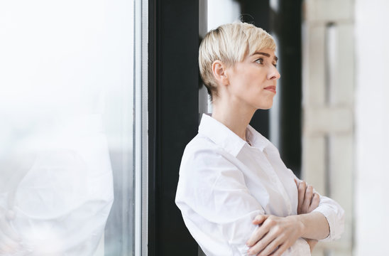 Anxious Entrepreneur Woman Thinking Standing Near Window In Modern Office
