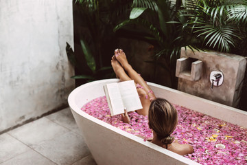 Woman reading book while relaxing in bath tub with flower petals