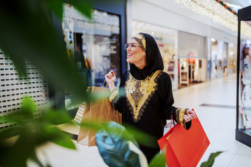 Excited attractive muslim woman walking in shopping mall with shopping bags in hands and looking for another pretty dress for her.