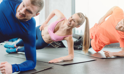 Fitness woman and men in the health club doing a side plank
