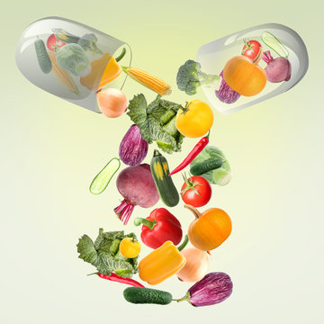 Capsule with falling vegetables on green background