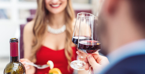 Couple toasting with red wine in romantic restaurant