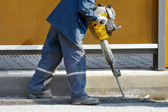 Worker with pneumatic demolition hammer breaking asphalt at road construction site. Man drilling and repairing concrete driveway surface with plugger hammer. Road repairing works with jackhammer