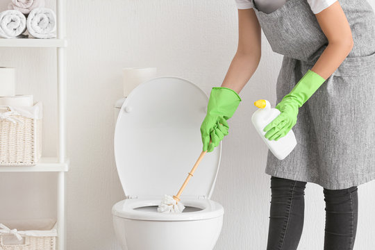 Young woman cleaning toilet in bathroom