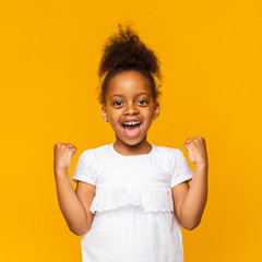 Cute black girl celebrating success, clenching fists