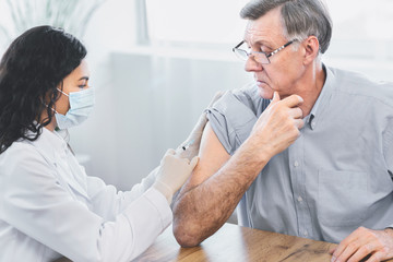 Obraz Mexican doctor doing vaccination to elderly man - fototapety do salonu