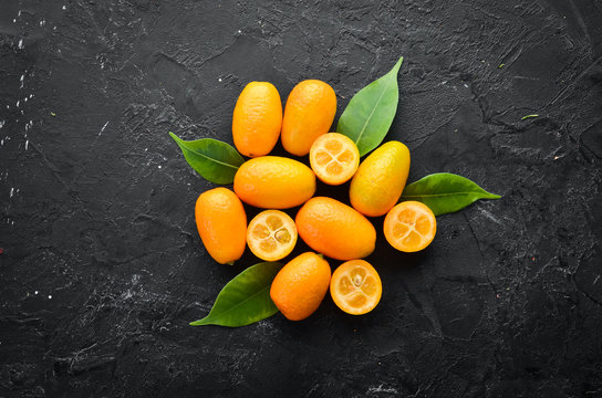 Kumquat on a black stone background. Citrus fruits. Top view. Free space for your text.