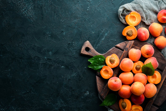Fresh apricots with green leaves on a black background. Rustic style. Top view. Free space for your text.