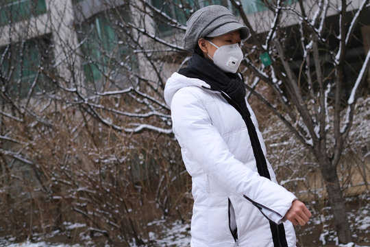 A woman wearing a face mask walks at a residential complex after a snowfall, as the country is hit by an outbreak of the new coronavirus, in Beijing