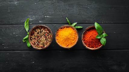 Wall Mural - Large spice and herb collection in bowls and spoons. Indian spices. On a black wooden background. Top view.
