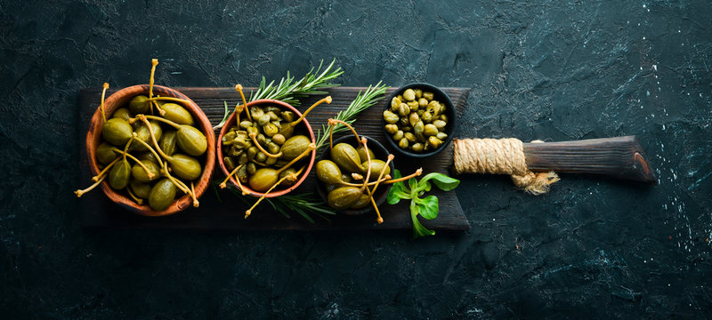 Capers. Marinated capers in a bowl on a black stone background. Top view. Free space for your text.