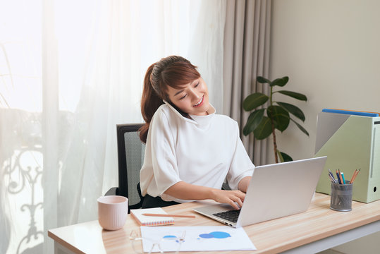Young Asian woman using her cellphone while using laptop and working from home
