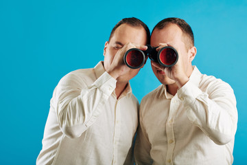 Unrecognizable twin brothers wearing white shirts looking through binoculars at camera, blue wall background