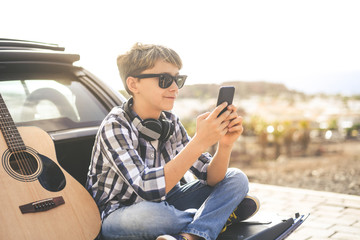 Teenager communicate with smartphone sitting outdoors after playing acoustic guitar. Young boy sharing multimedia content on line with friends. New technology, youth, music, and communication concept