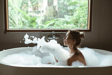 Obraz Woman relaxing in foam bath with bubbles in dark bathroom by window - fototapety do salonu