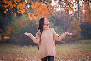 Woman in beige jumper, autumn nature, happy