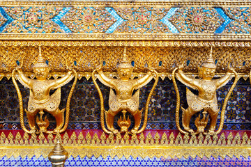Golden garuda and naga statue, decoration on a wall of The Emerald Buddha temple, Wat Phra Kaew, Grand Palace, Bangkok, Thailand.