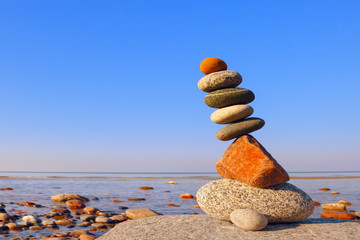 Balanced Rock Zen on the background of the sea. The concept of fall risk and unstable equilibrium.