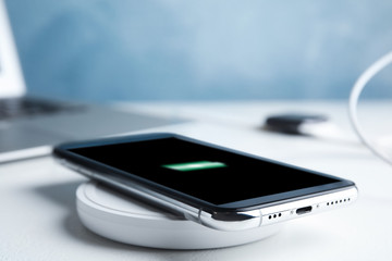 Mobile phone charging with wireless pad on white stone table, closeup. Space for text