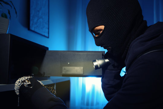 Thief taking jewelry out of steel safe indoors at night