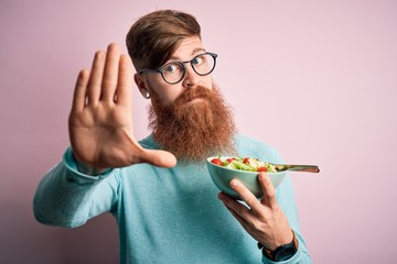Redhead Irish healthy man with beard eating vegetarian green salad over pink background with open...