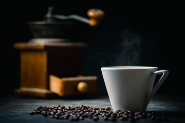 White hot coffee and coffee beans on the background of coffee grinders.