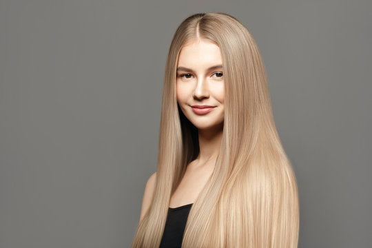 Beautiful young woman with long healthy hair posing against grey background. Beauty salon concept