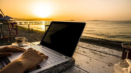 Keuken foto achterwand Chocoladebruin Freelance female hands working with laptop on wooden table on beach at sunset. Woman sitting on chair and using computer near blue sea shore at sunny day. Digital nomadism towards yellow sky & horizon