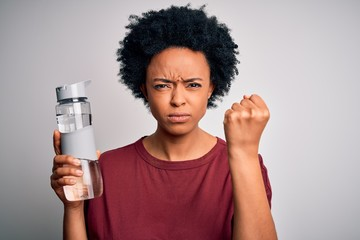 Young African American afro woman with curly hair drinking bottle of water for refreshment annoyed...
