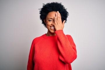 Young beautiful African American afro woman with curly hair wearing red casual sweater covering one...