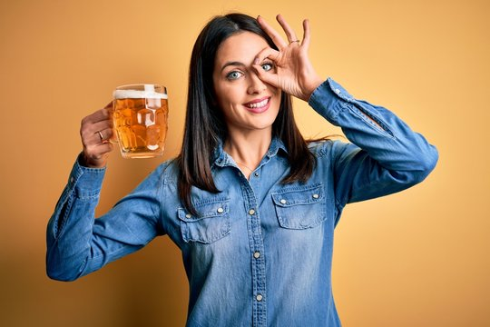 Young woman with blue eyes drinking jar of beer standing over isolated yellow background doing ok gesture with hand smiling, eye looking through fingers with happy face.
